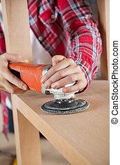 Carpenter Using Sander On Wooden Shelf