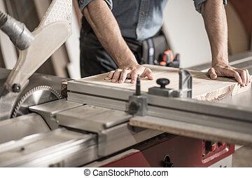 Carpenter using sawing machine - Closeup on carpenter's...