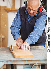 Carpenter Wearing Ear Protectors While Using Table Saw