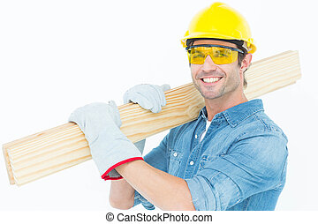 Carpenter wearing hardhat and glasses while carrying wooden ...