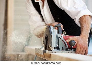 Carpenter with a circular saw - Close-up of a carpenter...