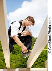 Carpenter with a folding ruler measuring beams - Carpenter...