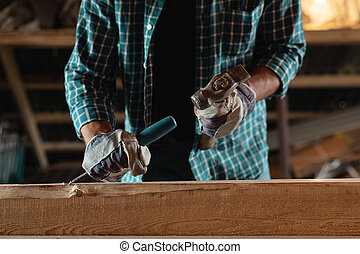 Carpenter with a hammer and chisel handles wood. Joiner at work in the workshop
