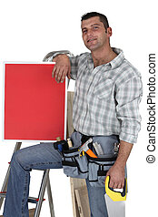 Carpenter with a red sign propped up on his knee