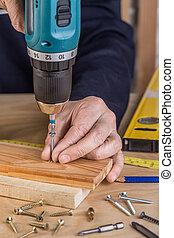 Carpenter with an electric screwdriver. carpenter at handmade work.