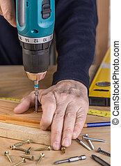 Carpenter with an electric screwdriver. carpenter at handmade work