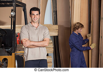 Carpenter With Arms Crossed In Workshop