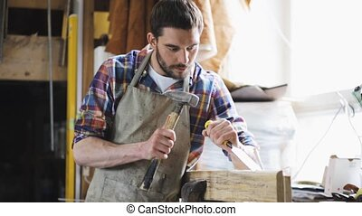 carpenter with chisel working at workshop - profession,...