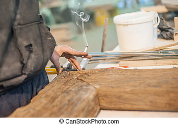 Carpenter with cigarette