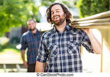 Mid adult carpenter with coworker carrying wooden planks while laughing outdoors