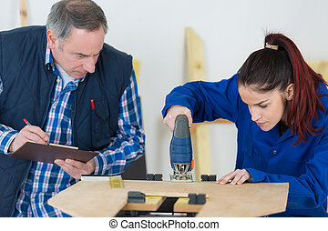carpenter with female apprentice working on building site