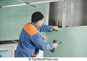 carpenter with gypsum plasterboard and screwdriver -...
