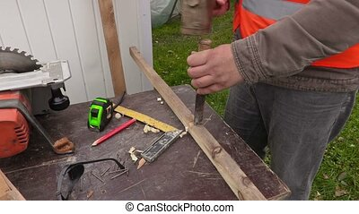 Carpenter with hammer and chisel