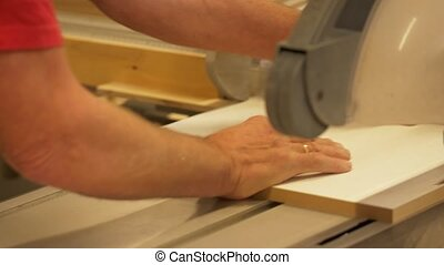 carpenter with panel saw and fibreboard at factory -...
