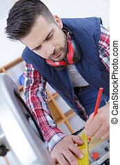 carpenter with ruler measuring wood plank at workshop