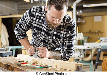 Carpenter work with plane on wood plank in workshop - Hard ...