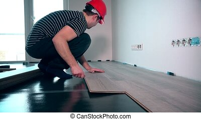 carpenter worker installing laminate flooring in the room....