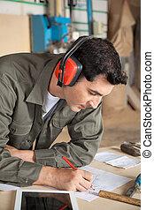 Carpenter Working On Blueprint In Workshop