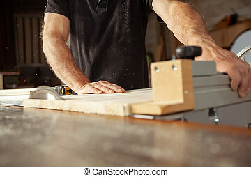 Carpenter working with a bench saw cutting planks