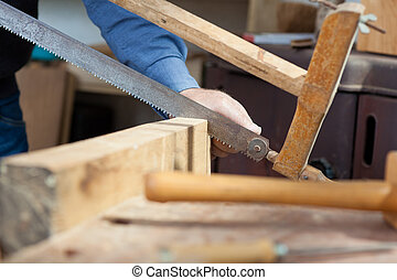 Carpenter working with a saw in the workshop