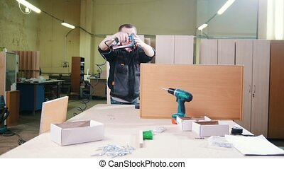 Carpenter working with an electric industrial stapler on the...