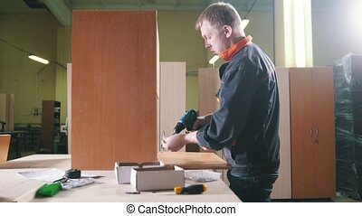 Carpenter working with an electric screwdriver on the factory, fixing furniture details