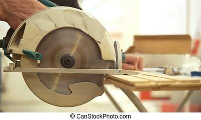 Carpenter working with circular blade sawing the wooden...