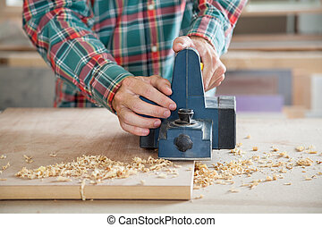 Carpenter Working With Electric Planer On Wood