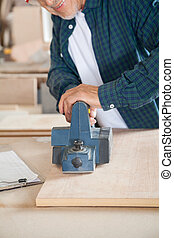 Carpenter Working With Electric Planer In Workshop