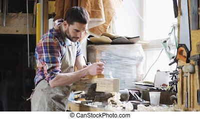 carpenter working with plane and wood at workshop -...
