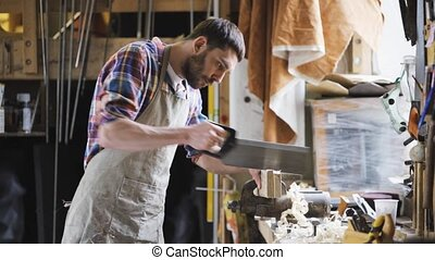 carpenter working with saw and wood at workshop -...