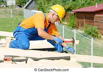 Carpenter works on roof - construction carpenter worker...