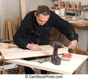 Carpenter - Young carpenter making measure with meter in ...