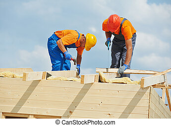 carpenters at wooden roof work - Two construction carpenters...