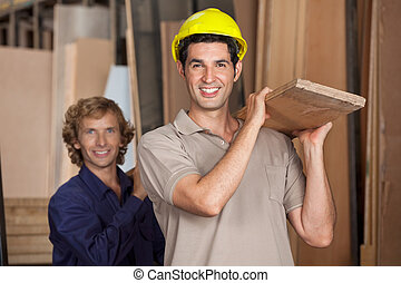 Carpenters Carrying Wooden Plank In Workshop