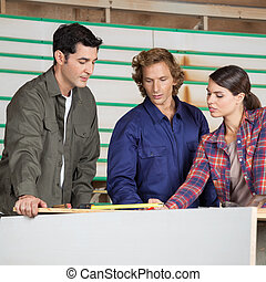 Carpenters Communicating At Table In Workshop