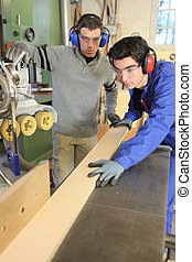 Carpenters cutting a plank of wood