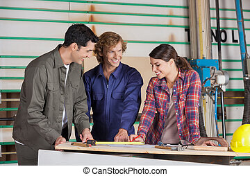 Carpenters Discussing Over Blueprint At Table