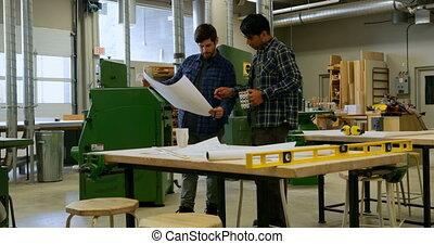 Carpenters discussing over blueprint in workshop 4k
