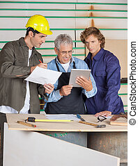 Carpenters Discussing Over Digital Tablet And Paper
