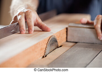 Carpenter's hands cutting wood with tablesaw in workshop