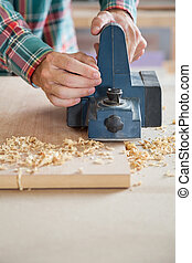 Carpenter's Hands Using Electric Planer On Wood