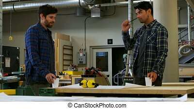 Carpenters interacting with each other in workshop 4k - ...