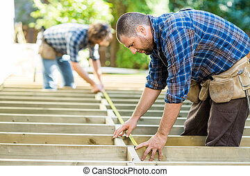 Carpenters Measuring Wood With Tape At Construction Site -...