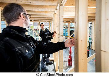 Carpenters Measuring Wooden Pillars At Site