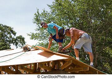 Carpenters Nailing Plywood - Carpenters use a pneumatic nail...
