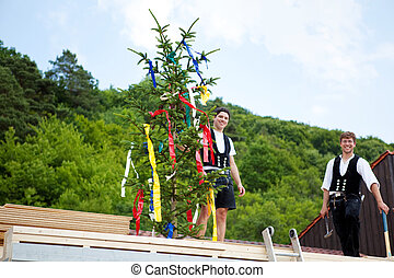 Carpenters performing the Topping Out ceremony after placing...