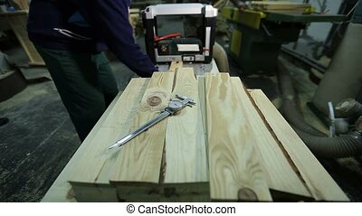 Carpenters planing planks with planing machine