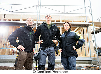 Carpenters Standing With Hands On Hips Against Incomplete Buildi