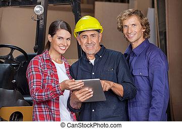 Carpenters Using Digital Tablet In Workshop